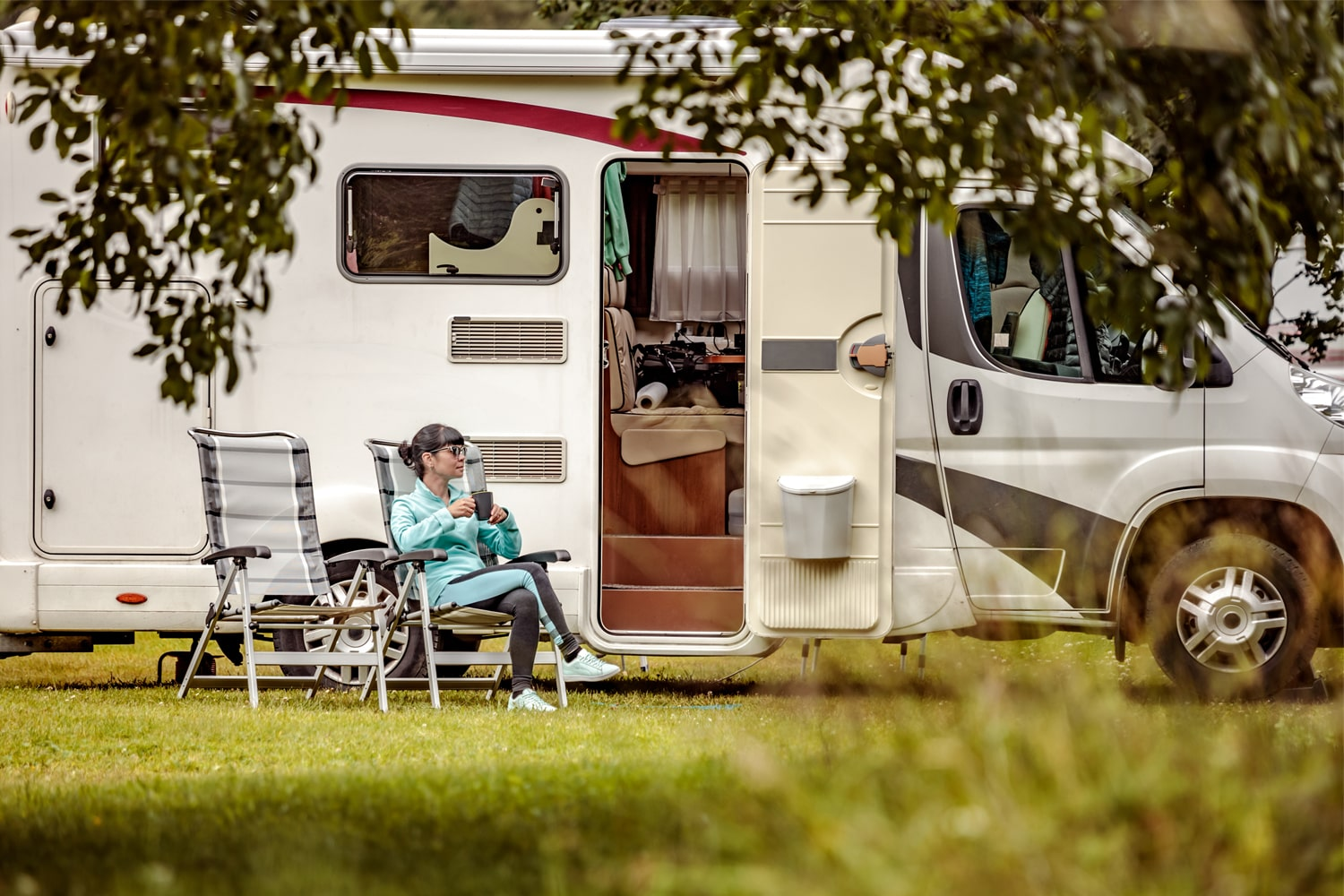 woman relaxing in front of RV