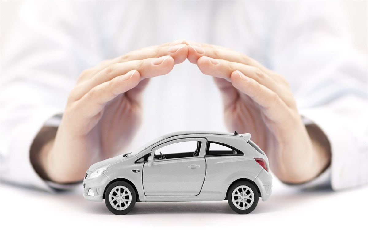 man shielding a mini car with his hands