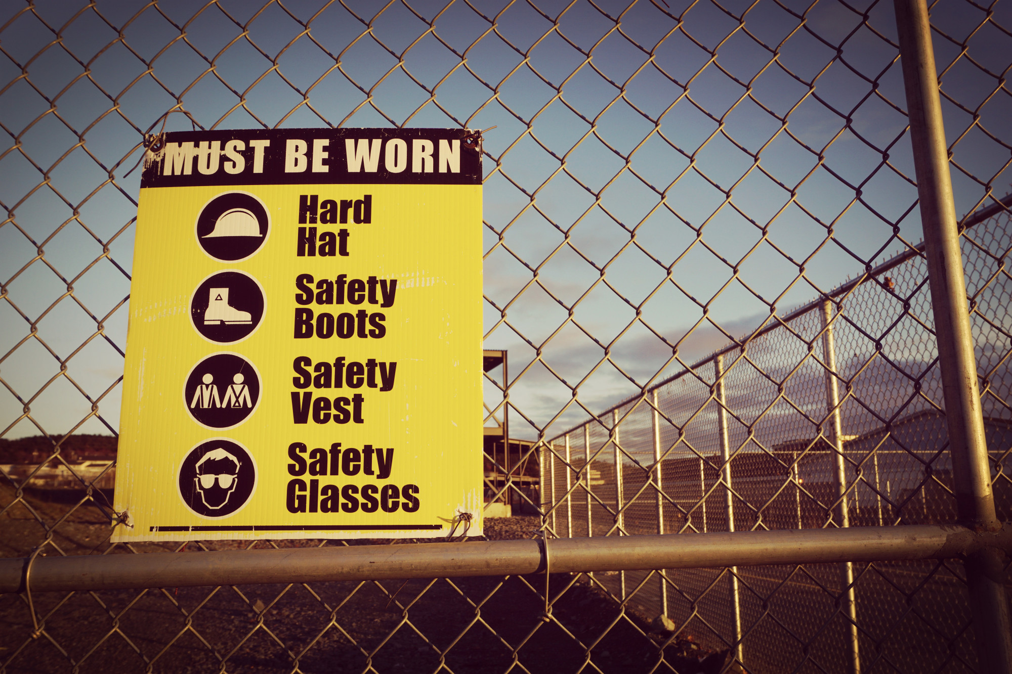 wire fence with safety signs for workers