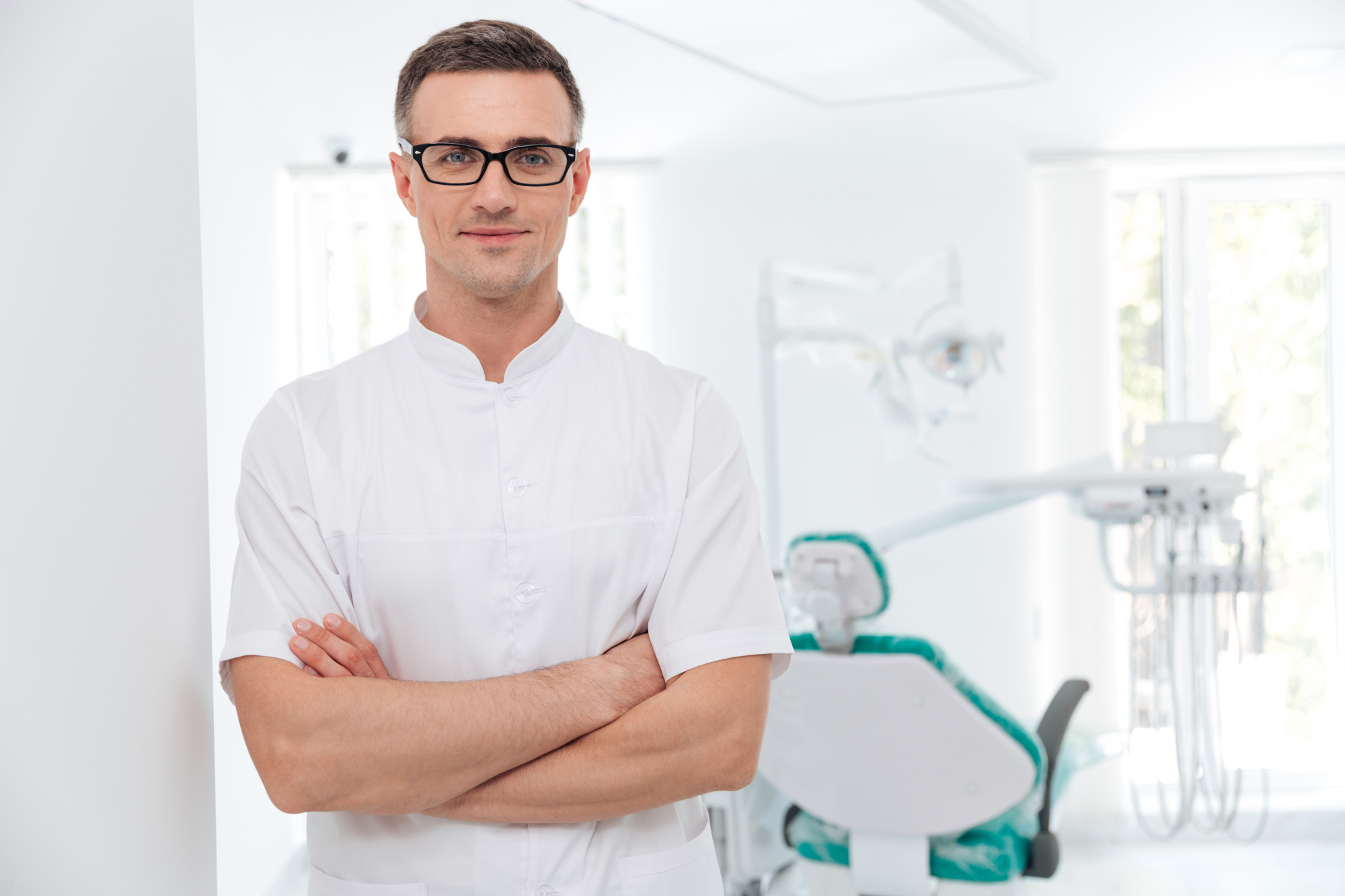 Male dentist standing with his hands crossed and looking at camera