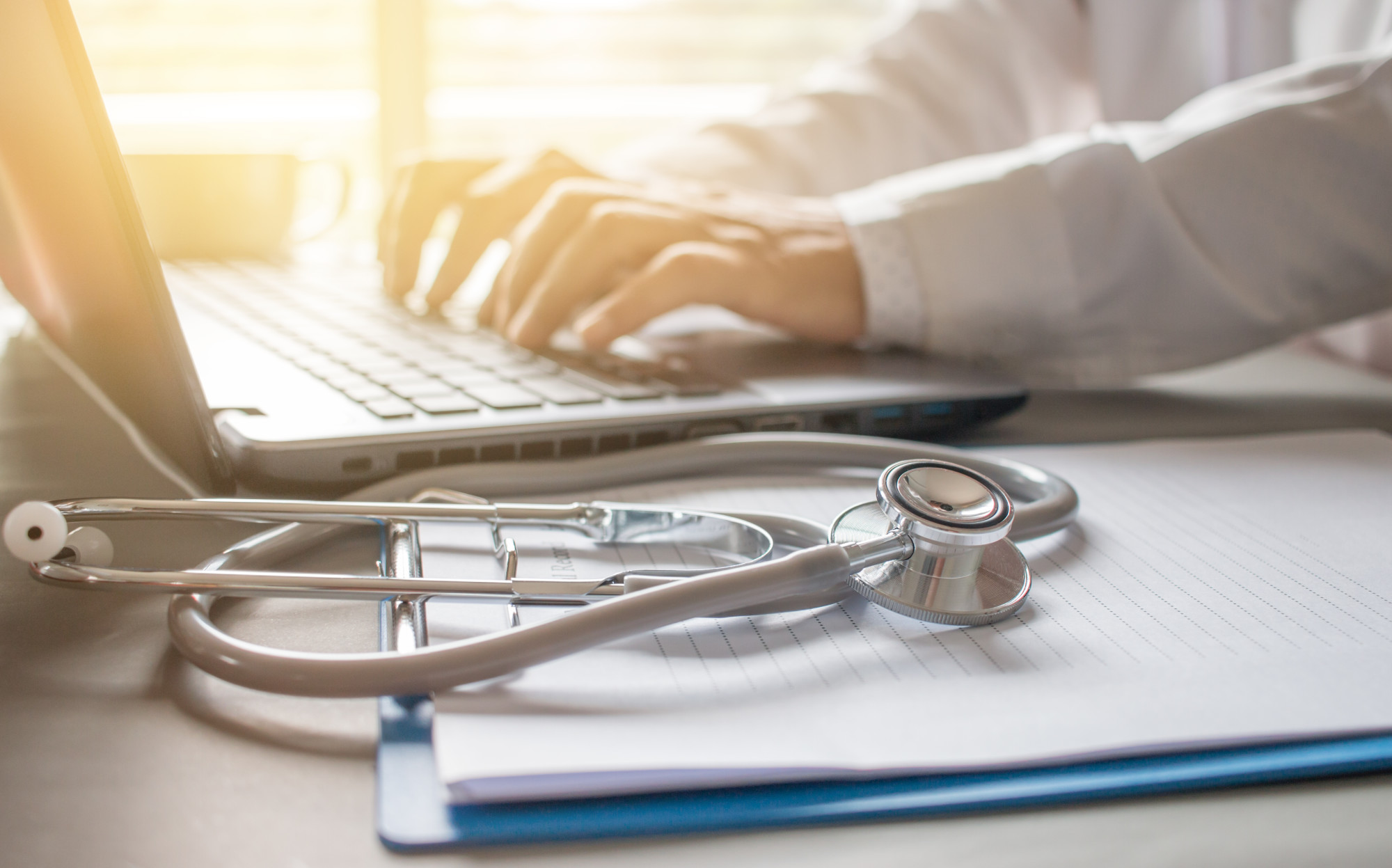 doctor typing on a laptop with a medical chart and stethoscope on the table