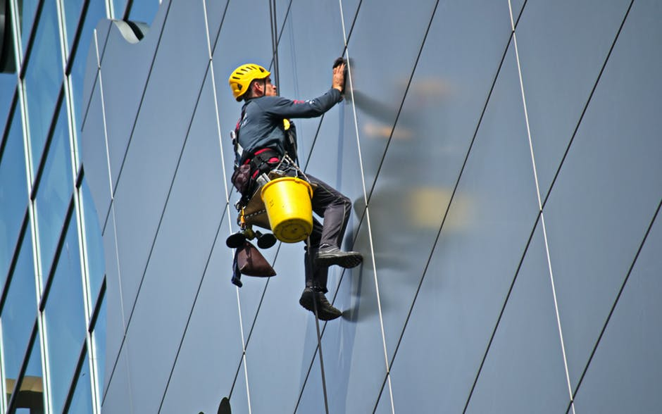man cleaning building windows while hanging