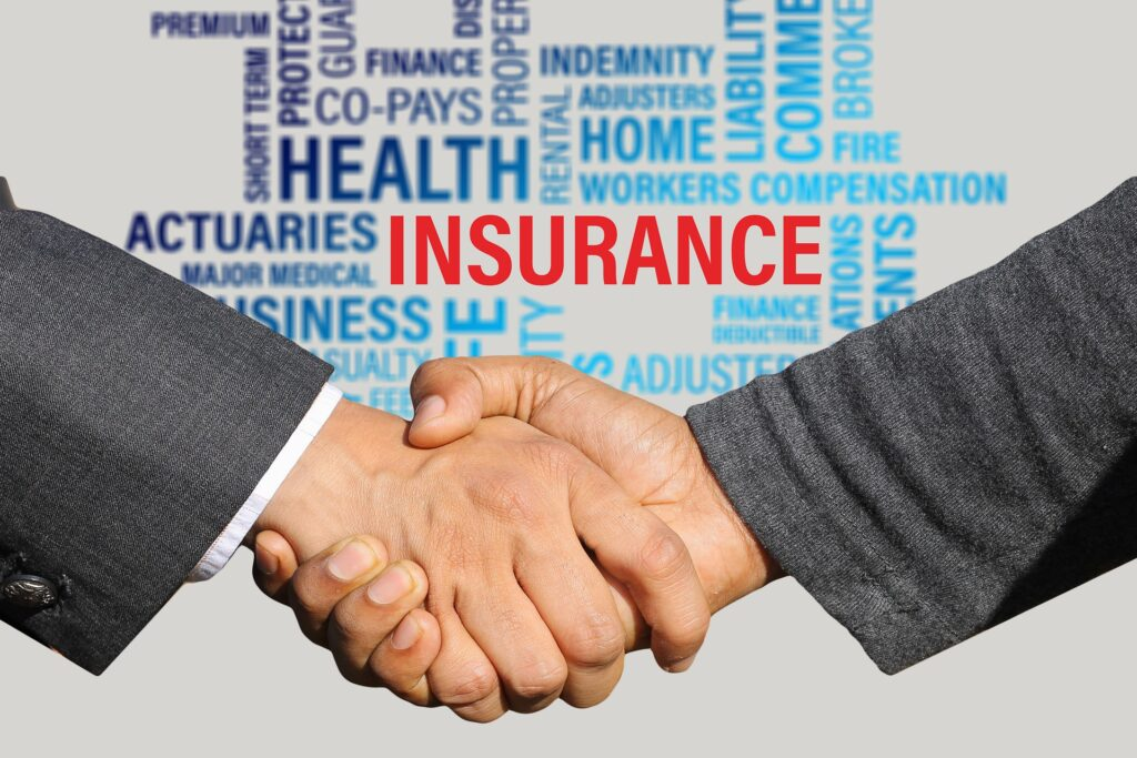 client and insurance broker shaking hands with a background image of insurance terms
