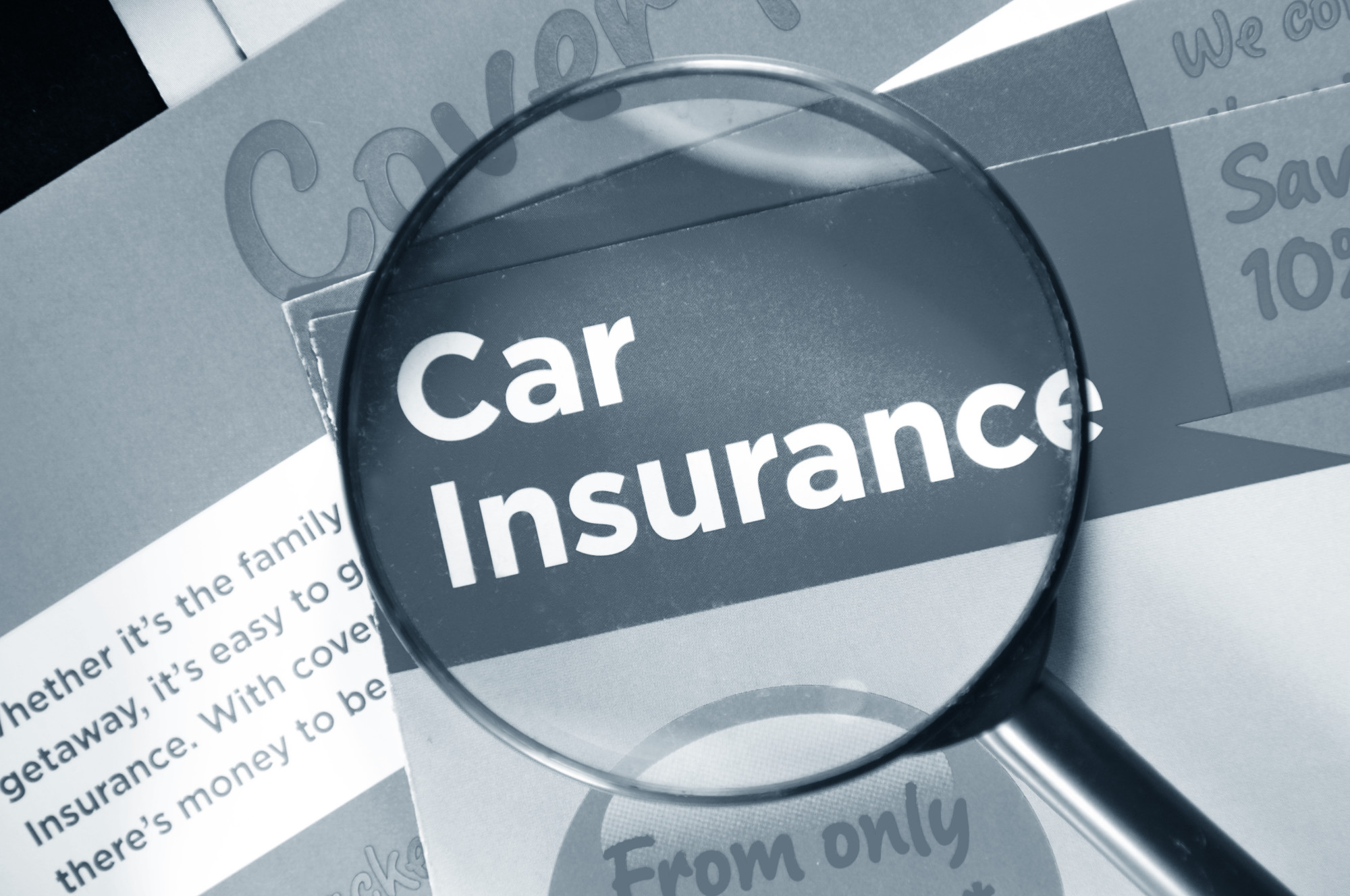 magnifying glass on top of car insurance title on a brochure