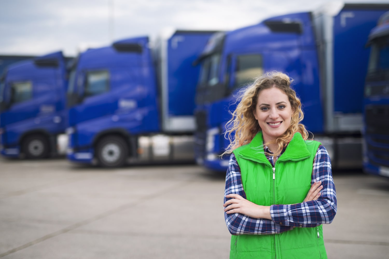 Woman standing in front of a fleet of trucks