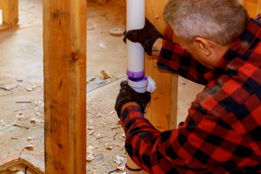 Man fixing sewer pipe