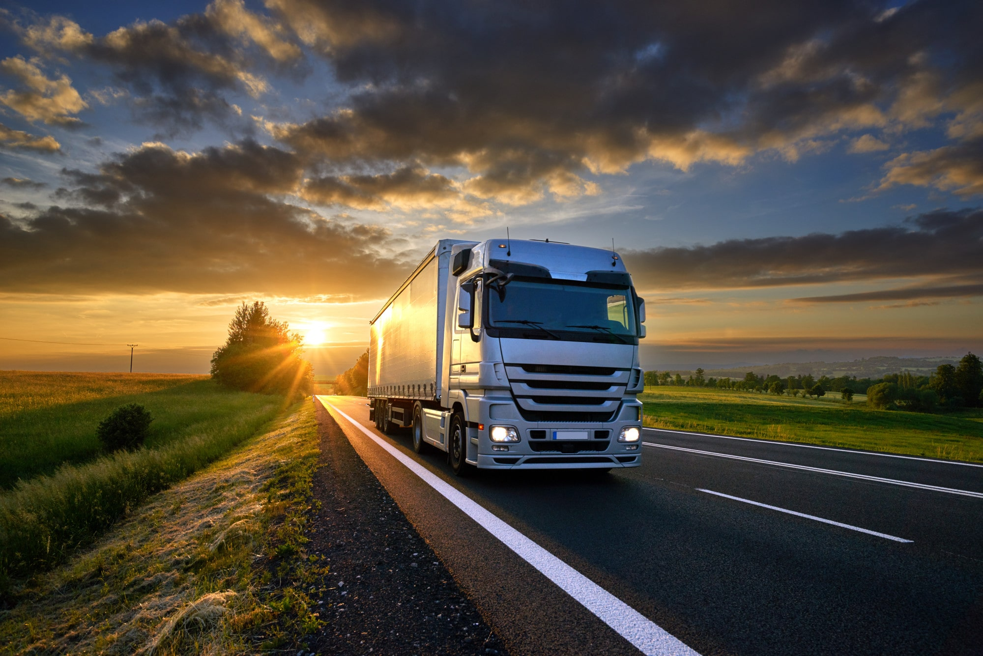 Truck driving on the asphalt road in rural landscape at sunset with dark clouds
