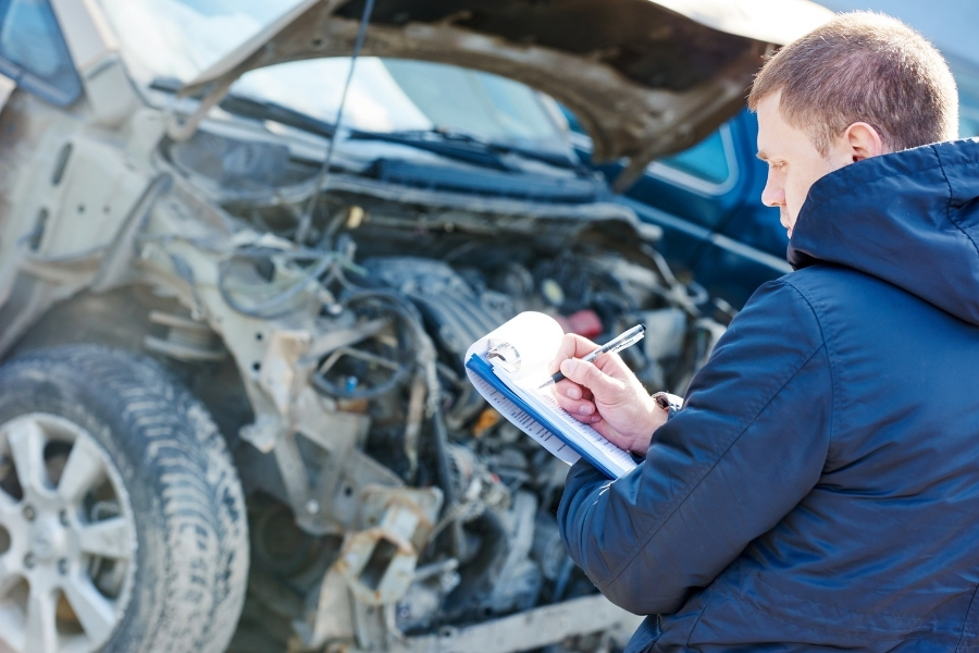 Mechanic checking the status of a damaged vehicle