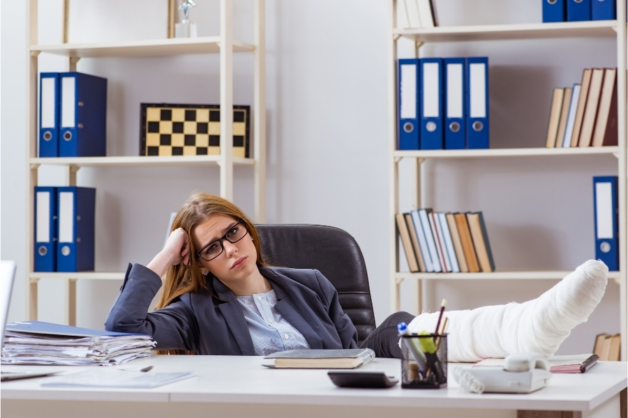 Woman in office sitting with her injured leg on top of her desk