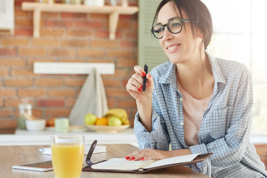 Indoor shot of smiling happy woman sits at kitchen table, makes notes in diary, plans what to do