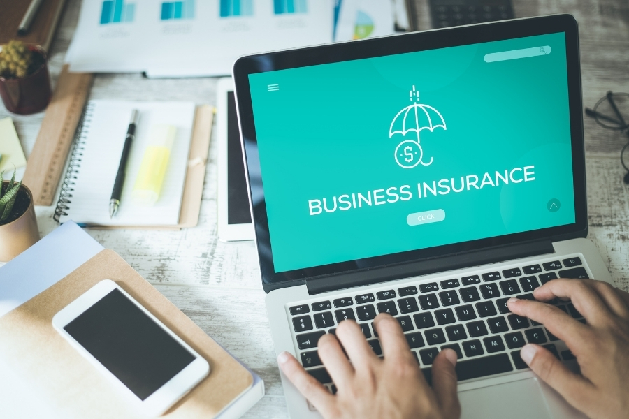 Business Insurance in Laptop Monitor on desk with mobile phone