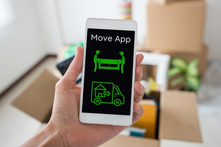 on phone using moving app with boxes in the background
