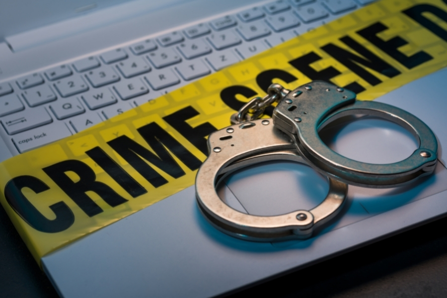 Crime scene tape on laptop with handcuffs on top