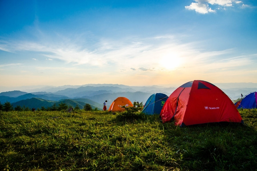 Tents pitched at the top of a mountain with blue sky view