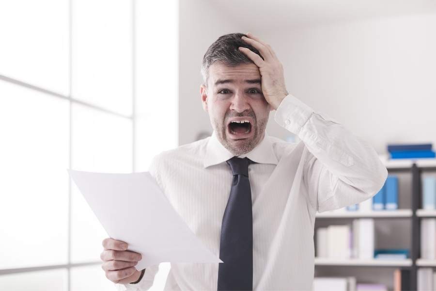 Man holding paper, confused and surprised