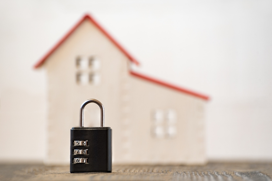 Home Safety Concept: Padlock in front of a model house