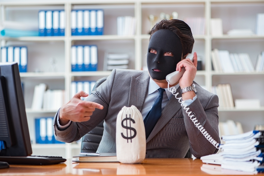 masked man calling on phone pointing at a bag of money