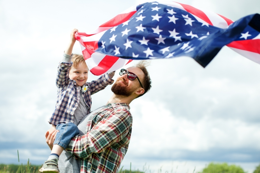 father carrying his son waving the american flag