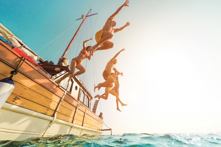 Group jumping in water from a boat
