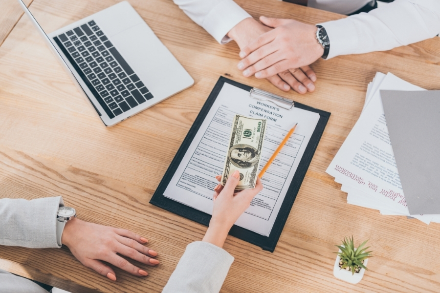 top view handing dollars on top of workers compensation claim form