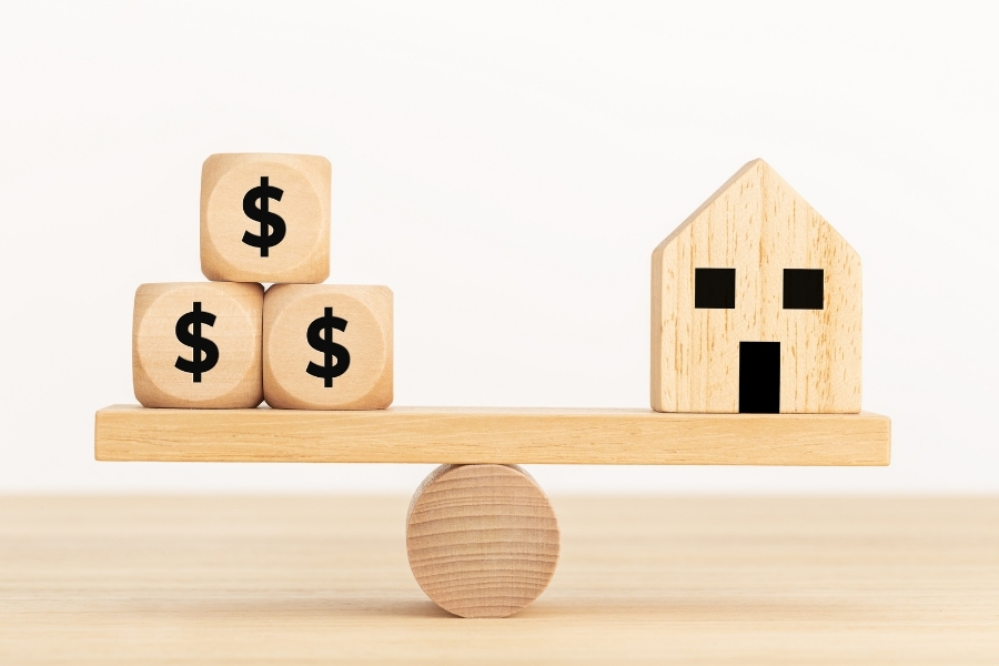 dollar blocks and house being balanced by a cylinder