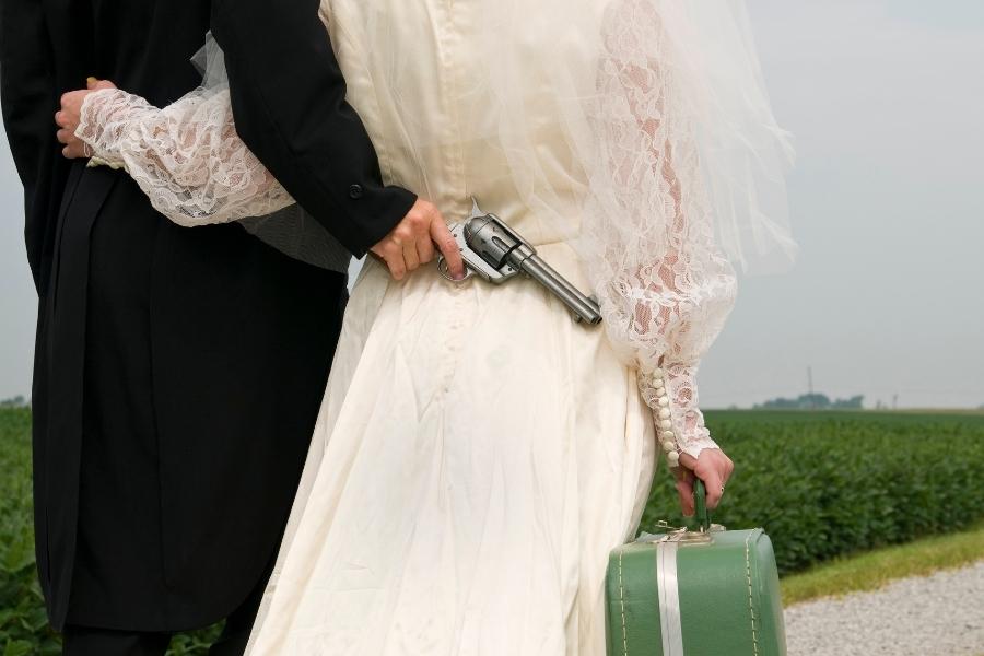 Man holding a gun behind his bride