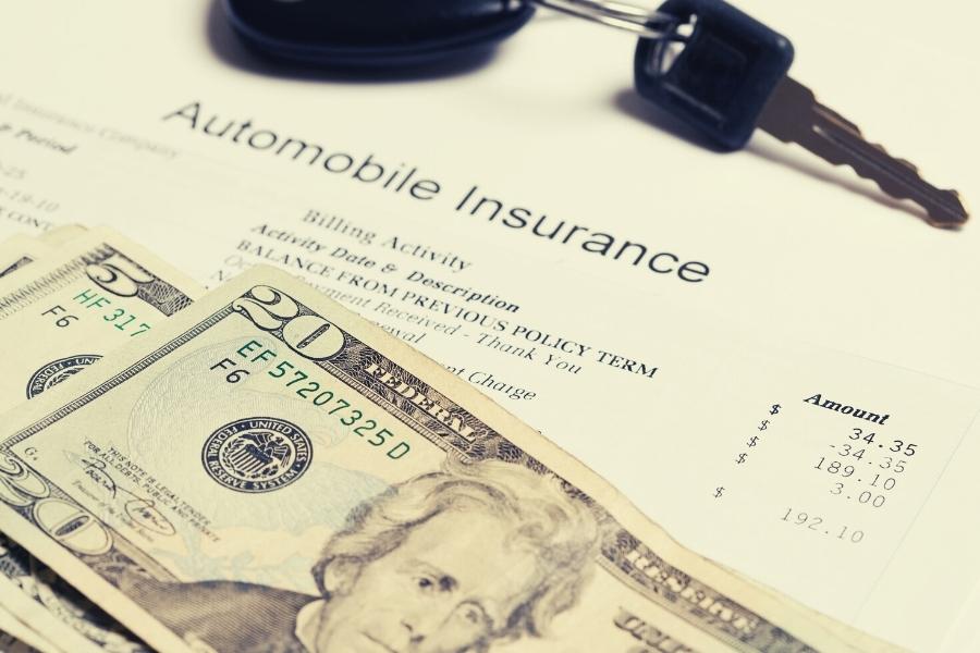 auto insurance document, dollars and keys
